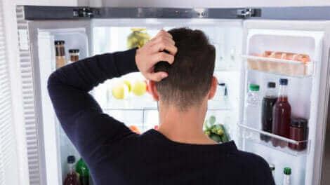 Un homme qui regarde la nourriture dans son réfrigérateur.
