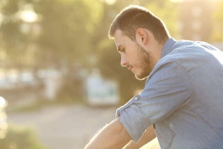 Un homme pensif assis en plein air.