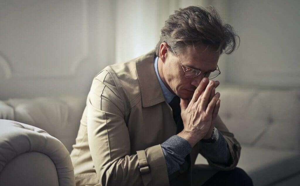 Un homme triste assis sur un canapé.