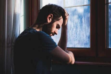 Un homme triste contre une fenêtre.