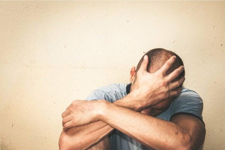 Un homme triste, main sur la tête.