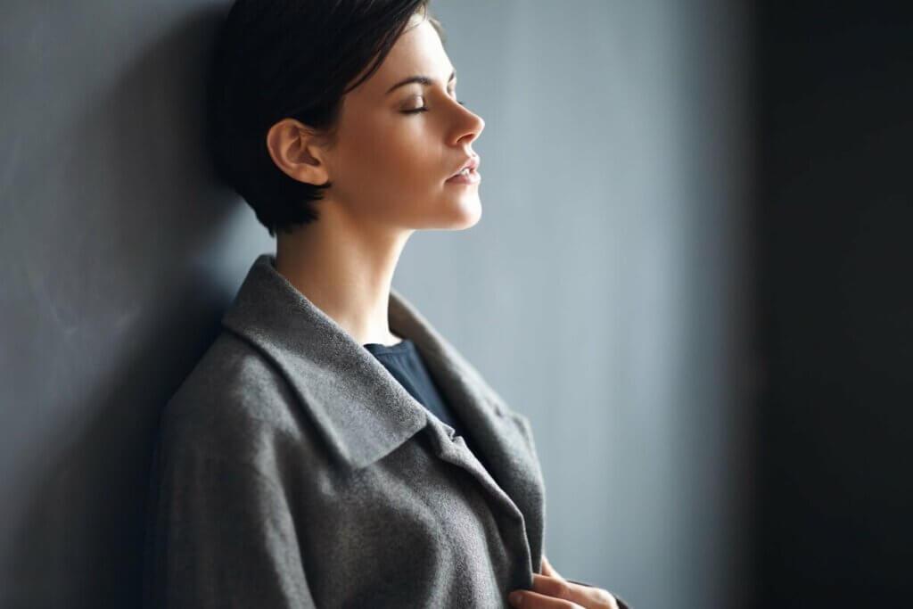 Une femme adossée contre un mur.