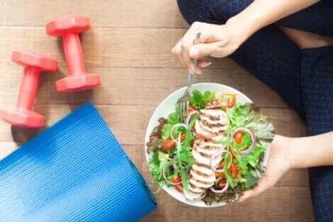 Une femme qui mange une assiette de salade.
