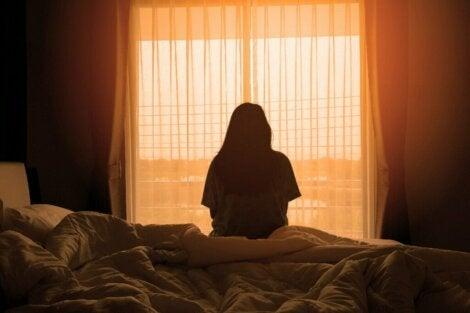 Une femme assise sur son lit face à une fenêtre.
