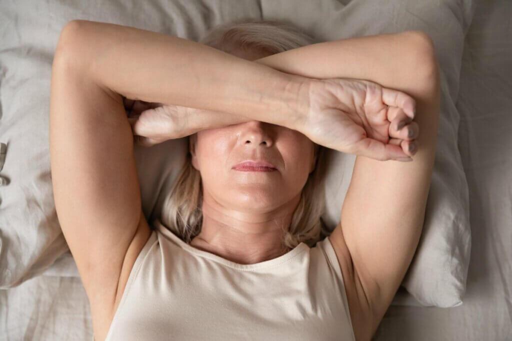 Une femme couchee sur son lit, les bras sur ses yeux.