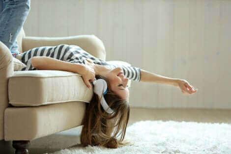 Une femme qui écoute de la musique affalée sur un canapé.