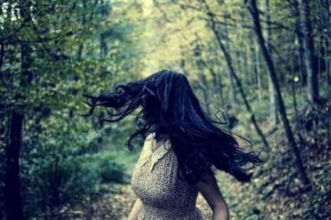 Une femme dans les bois qui semble avoir peur.