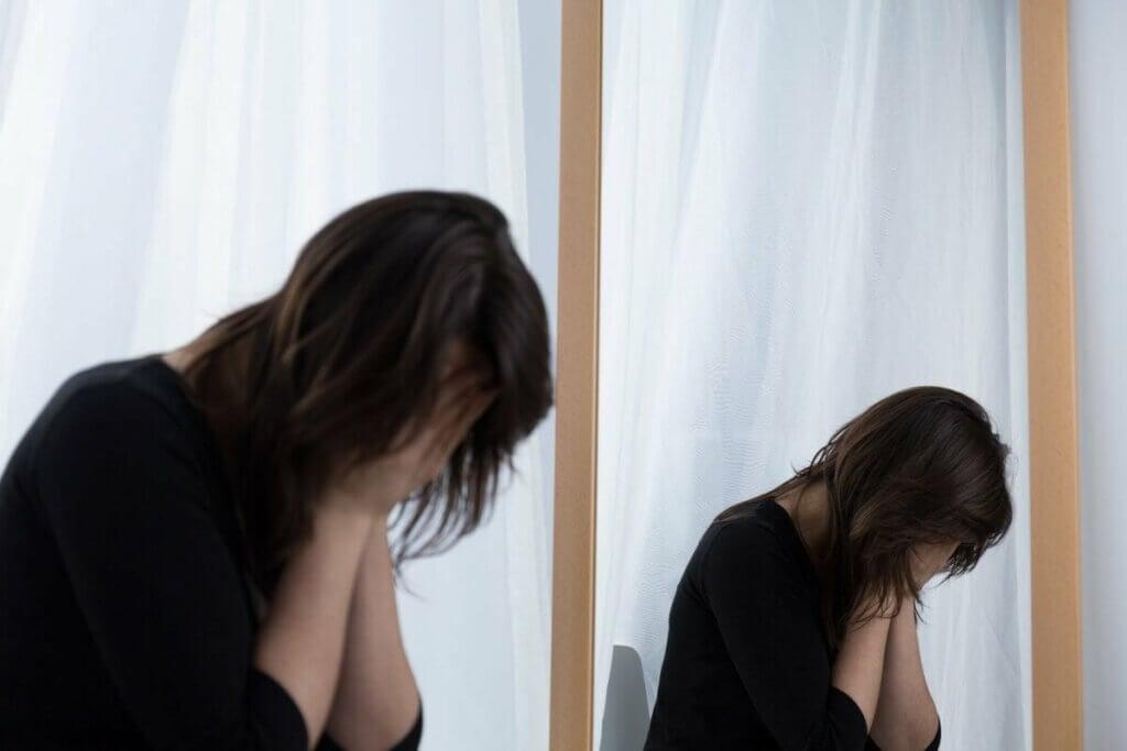 Une femme qui pleure près d'un miroir.