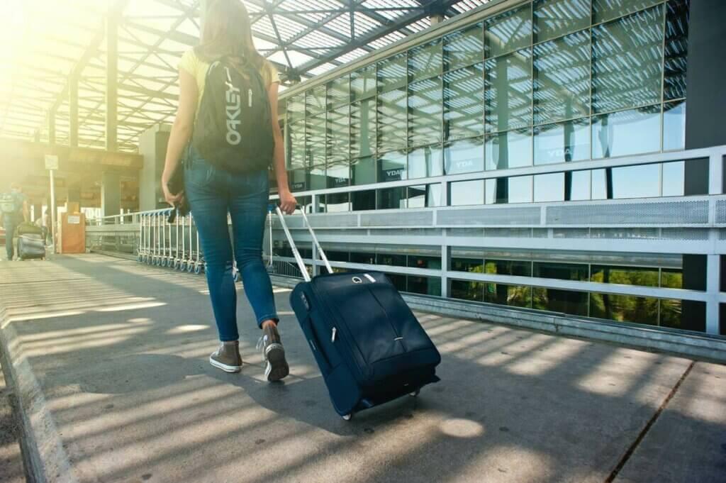 Une femme qui marche avec une valise.