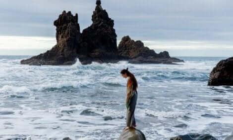 Une fille sur un rocher en pleine mer.