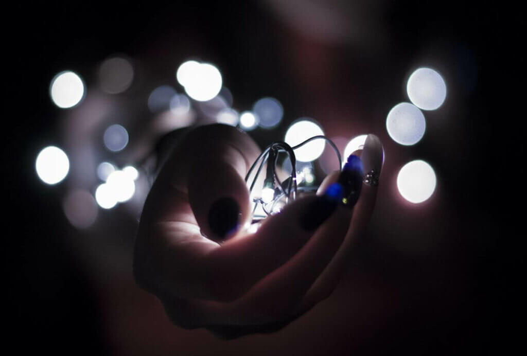 Une guirlande lumineuse dans une main.