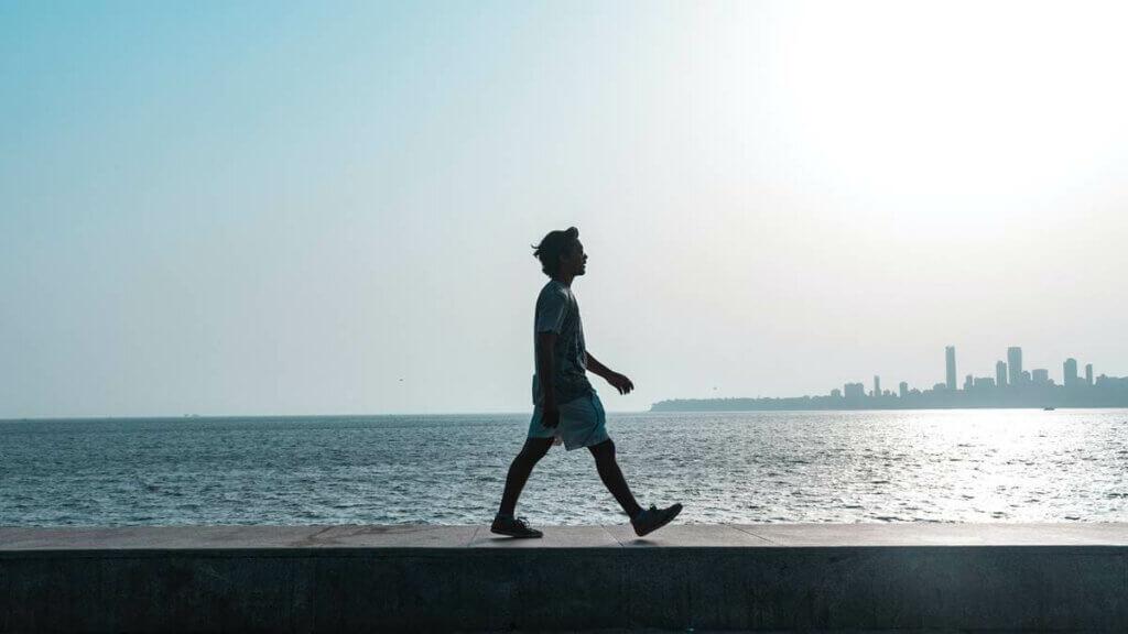 Un homme qui marche en bord de mer.