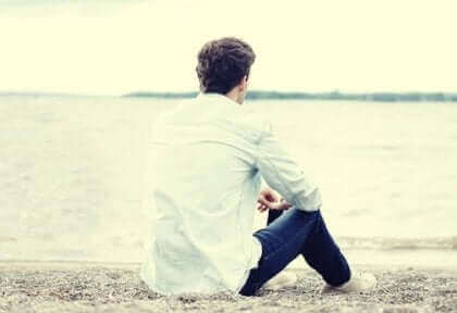 Un homme seul assis sur le sable.