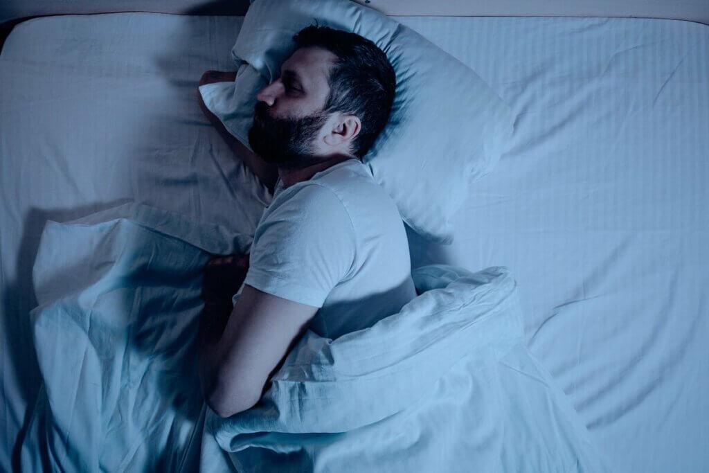 Un homme qui tente de dormir dans son lit.