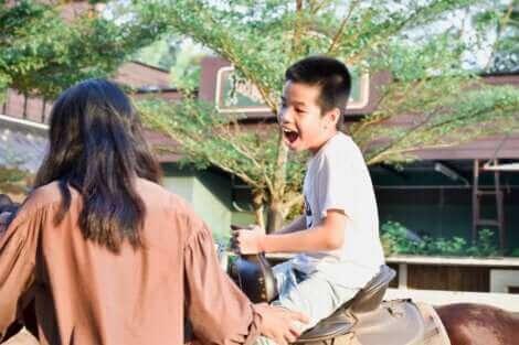 Un petit garçon qui fait du cheval.