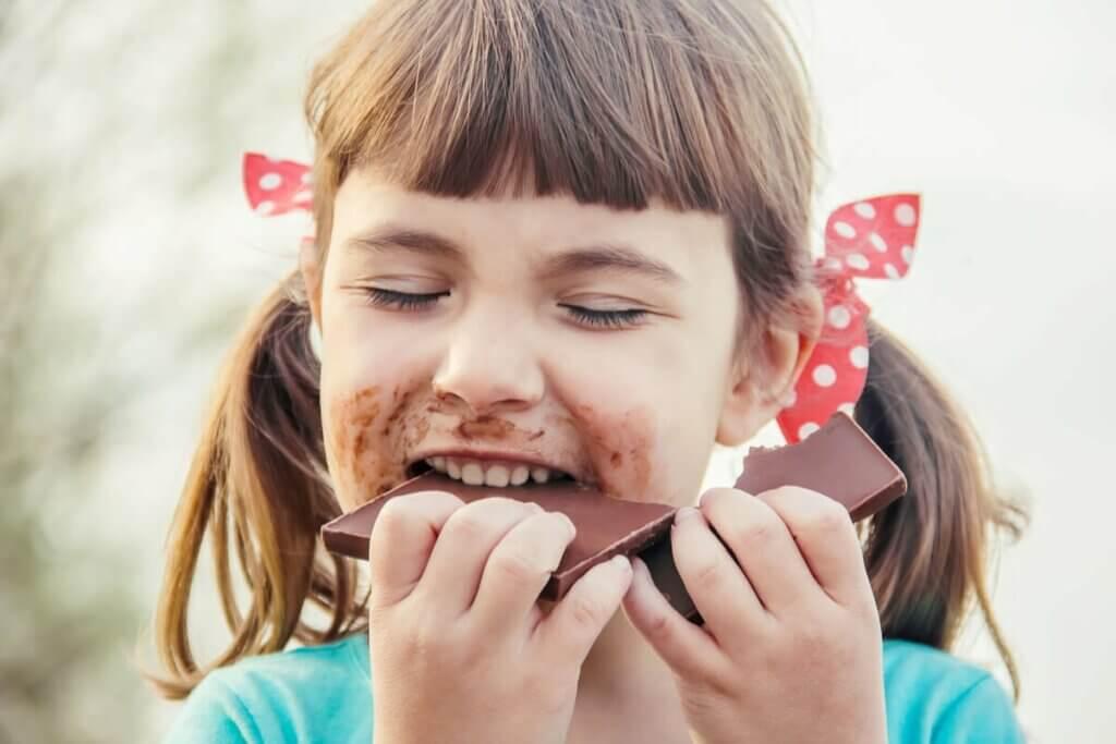 Une petite fille en train de manger du chocolat.