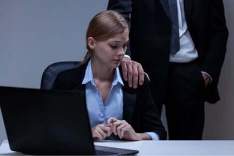 Un homme qui pose sa main sur l'épaule d'une collègue intimidée.