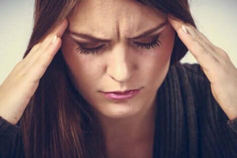 Une femme anxieuse qui a mal à la tête.