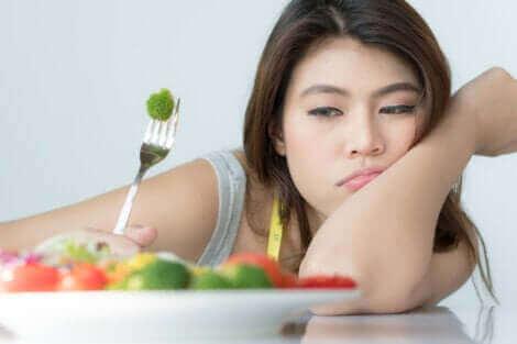 Une femme qui refuse de manger son assiette.