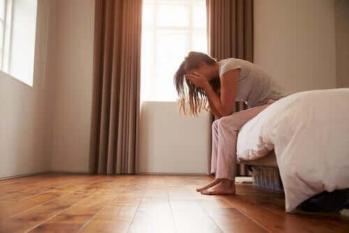 Une femme attristée sur son lit.