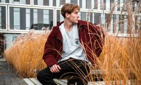 Un garçon assis sur un banc.