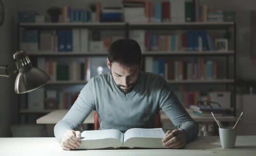 Un étudiant garçon en train de lire un livre.