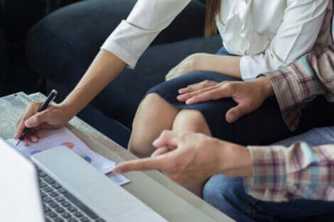 Un homme qui pose une main sur les genoux d'une collègue.