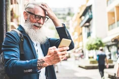 Un homme âge qui regarde son téléphone portable.