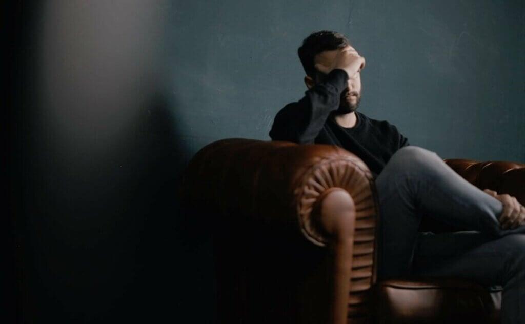 Un homme assis sur un canapé.