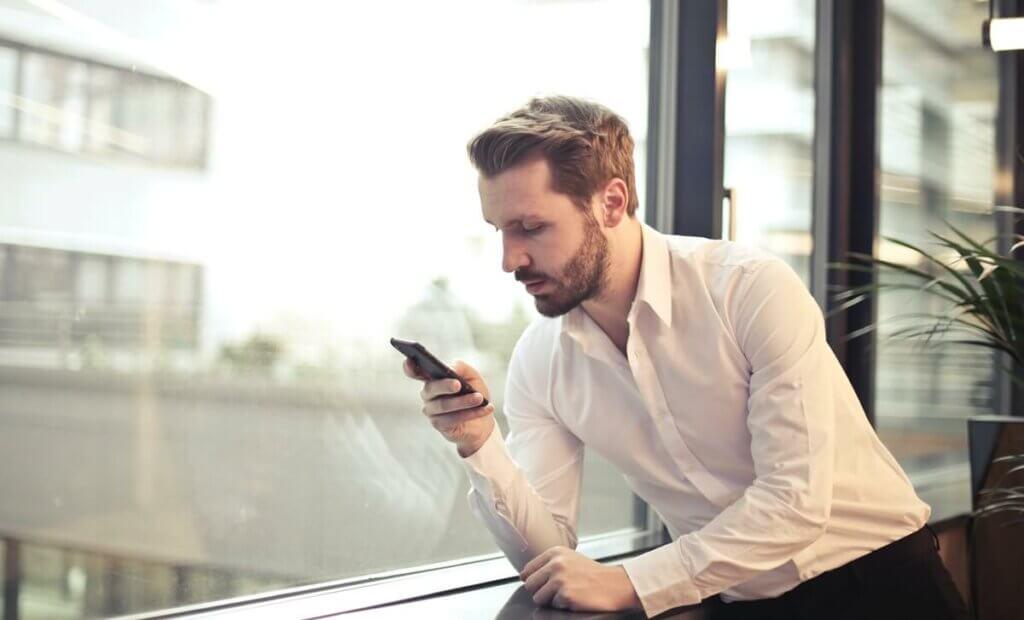 Un homme avec un téléphone portable en main.