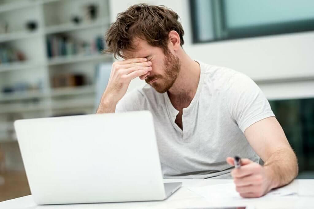 Un homme fatigué devant son ordinateur.