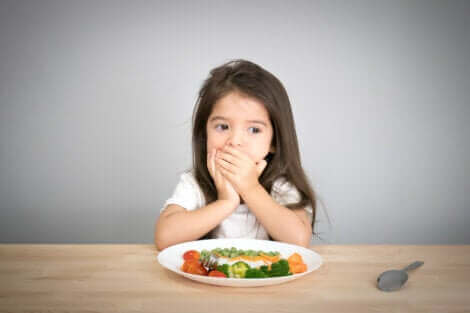Une petite fille qui refuse de manger son assiette.