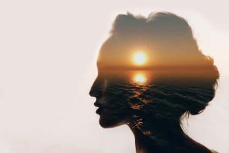 Tête d'une femme de profil avec une photo d'un coucher de soleil en transparence dans son cerveau.