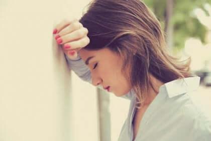 Une femme stressée qui pose sa tête contre un mur.