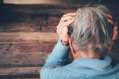 Une personne âgée, la tête entre ses mains.