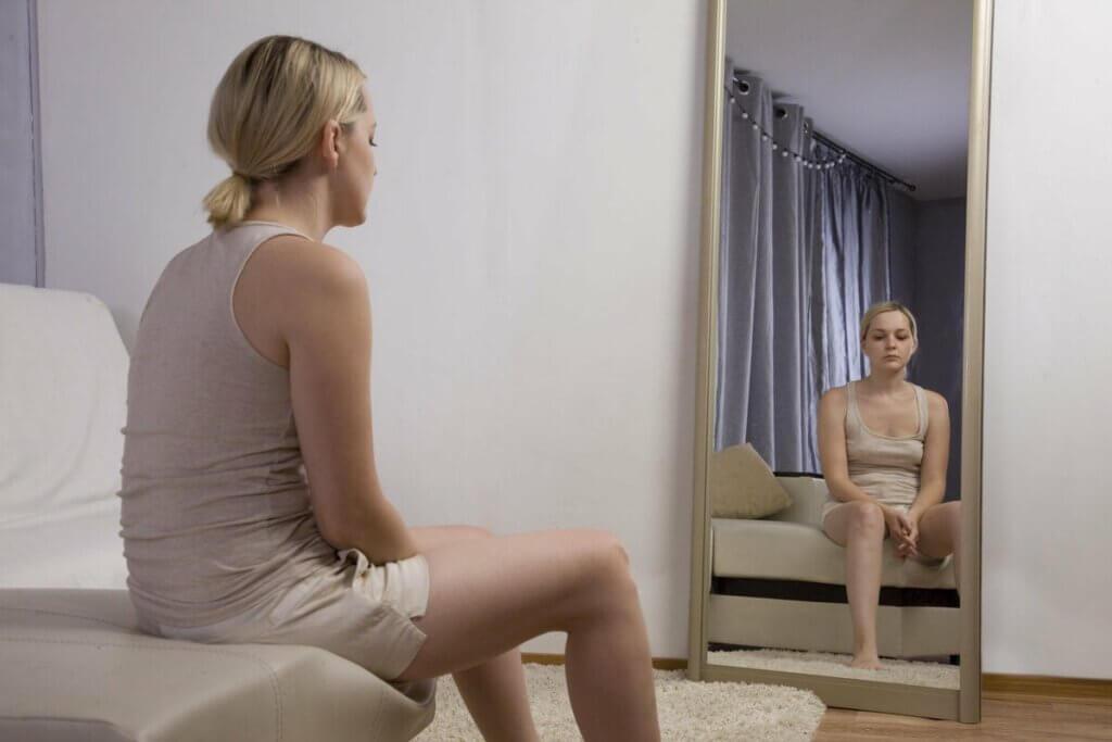 Une femme qui se regarde dans le miroir, l'air triste.