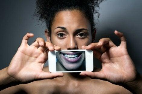 Visage d'une femme avec une photo d'un sourire sur l'écran de son téléphone.