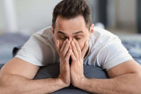 Un homme allongé qui se frotte les yeux.
