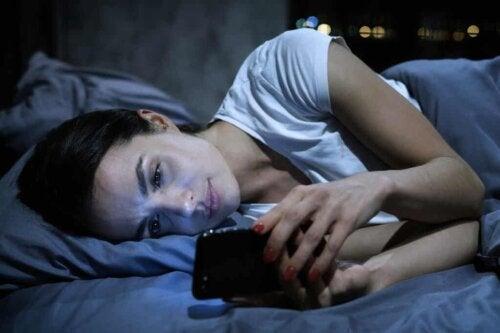 Une femme sur son portable dans le lit.