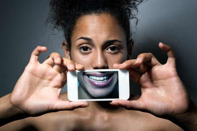 Une femme qui tient un téléphone entre ses mains.