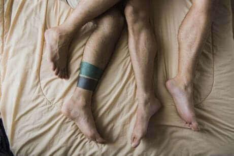 Des jambes d'hommes sur un lit.
