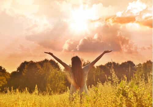 Une femme dans la nature qui lève les bras au ciel.