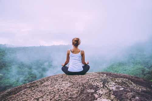 Une femme qui médite à la montagne.