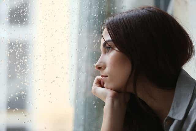 Femme qui regarde la pluie à travers la fenêtre.