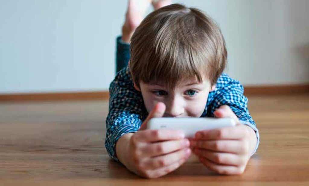Un enfant qui joue sur un smartphone.