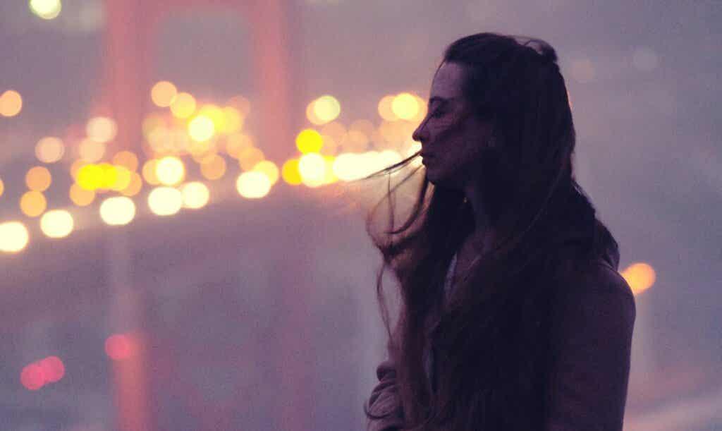 Femme près d'un pont la nuit.