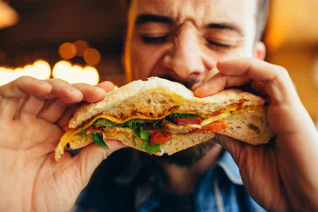 Un homme qui mange un sandwich.