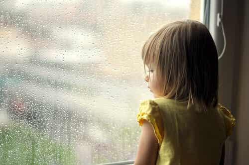 Petite fille qui regarde par la fenêtre.