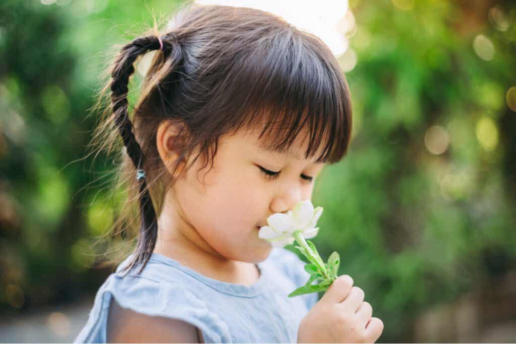 Une enfant qui sent une fleur.