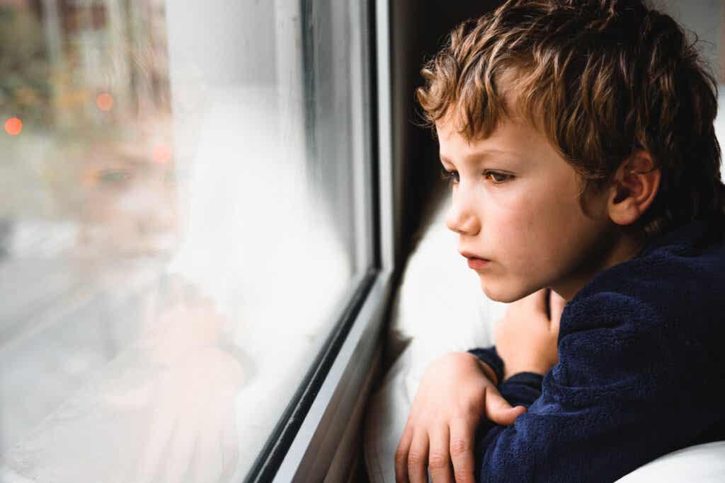 Enfant triste qui regarde par la fenêtre.